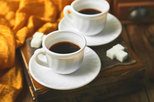 Dos tazas de café espresso cerca de un cubo de azúcar