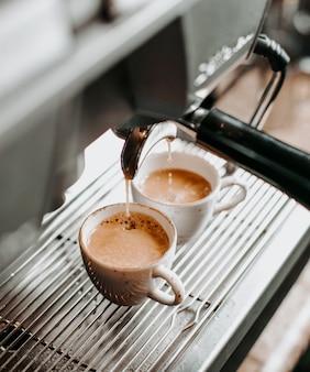 Dos tazas de café exprés debajo de la cafetera