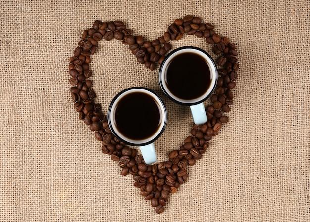 Dos tazas de café exprés en granos de café en forma de corazón.