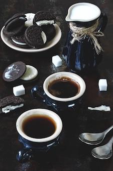Dos tazas de café expreso, una jarra de leche y galletas de chispas de chocolate con un relleno blanco.