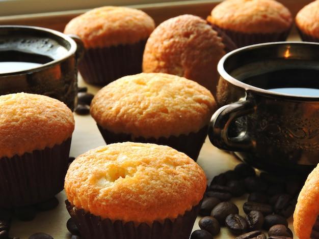 Dos tazas de café expreso, mini magdalenas, granos de café.