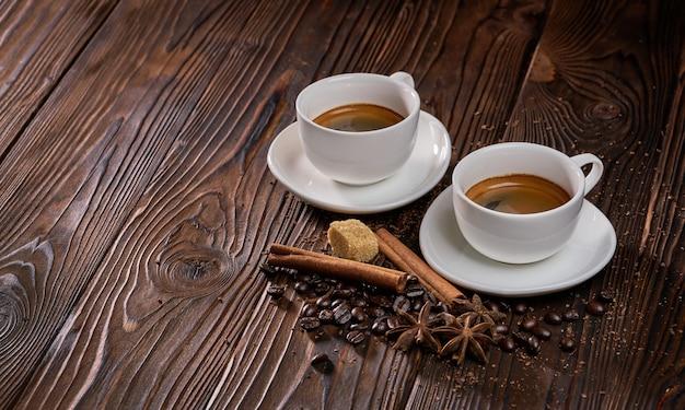 Dos tazas de café expreso recién hecho con granos de café sobre una mesa de madera rústica