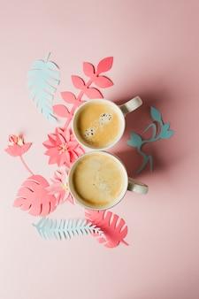 Dos tazas de café y flores de papel artesanal de origami moderno copian espacio