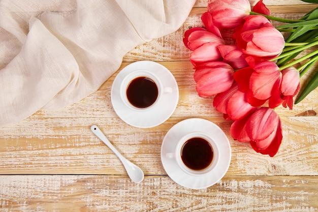 Dos tazas de café con flores de tulipán rosa