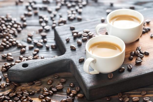 Dos tazas de café con granos de café.