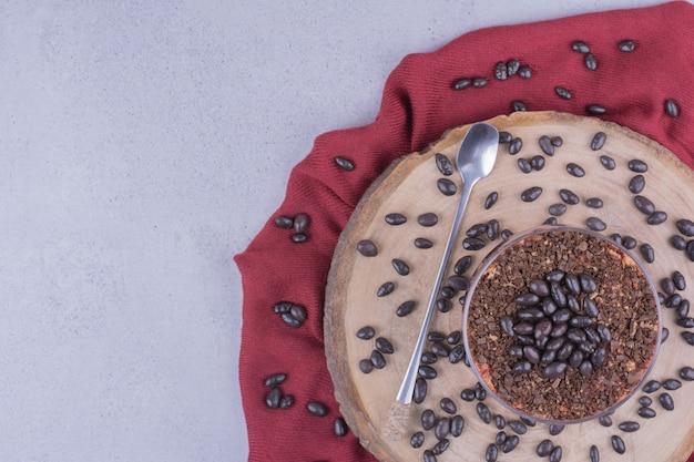 Dos tazas de café con granos de chocolate en una bandeja de madera