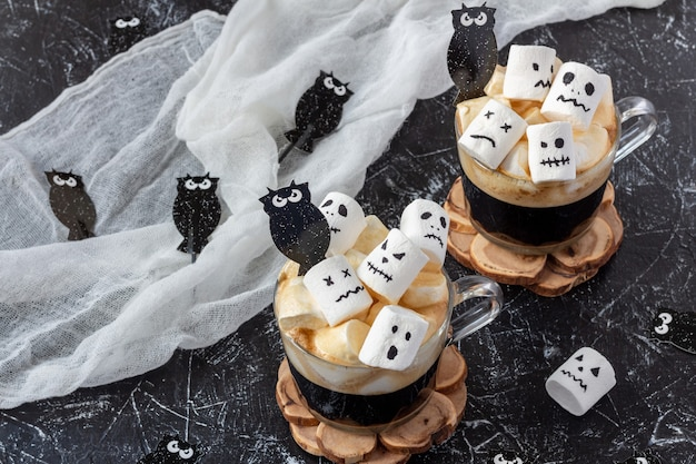 Dos tazas de café con malvavisco (caras espeluznantes, monstruo) en la mesa oscura para halloween