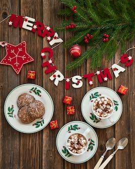 Dos tazas de café con malvaviscos y pan de jengibre en decoraciones navideñas