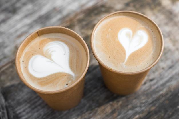 Dos tazas de café de papel con arte latte en forma de corazón