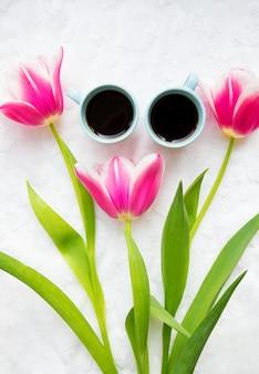 Dos tazas de café y un ramo de tulipanes rosados.