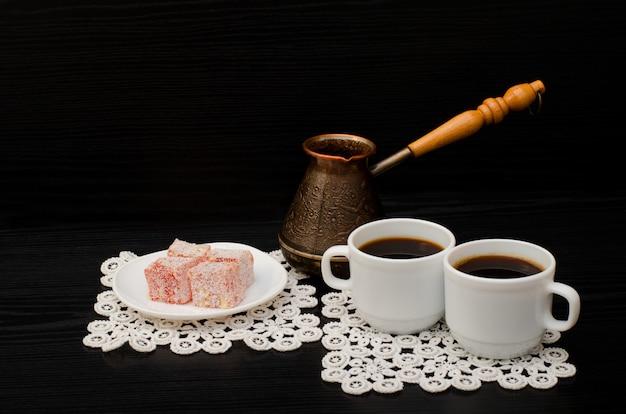 Dos tazas de café en las servilletas de encaje, ollas y postre turco sobre un fondo negro