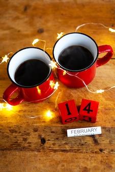 Dos tazas de café en tazas rojas en una pared de guirnaldas. desayuno matutino para san valentín. vista desde arriba.