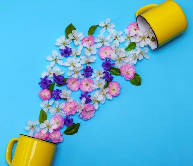 Dos tazas de cerámica amarilla y capullos de flores dispersos.