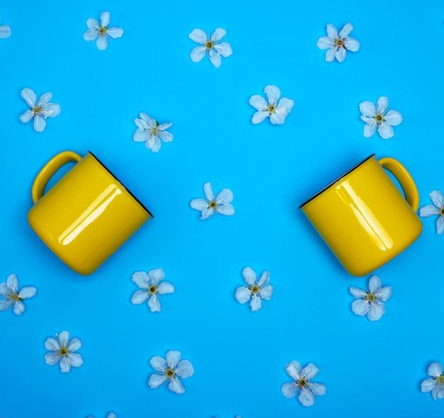 Dos tazas de cerámica amarillas en un azul