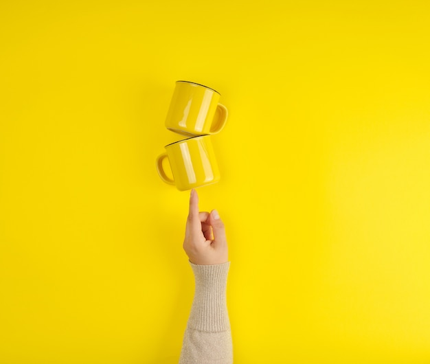 Dos tazas de cerámica amarillas están apoyadas por una mano femenina.