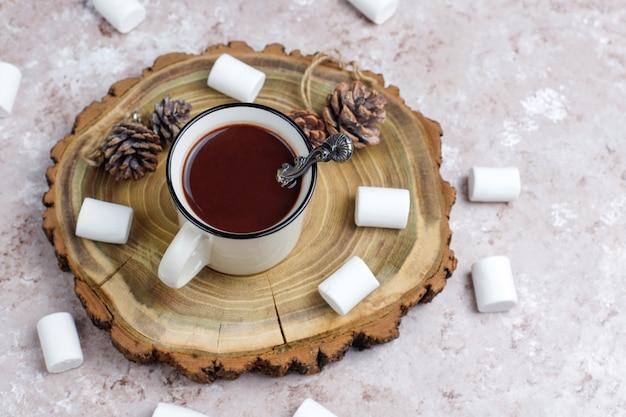 Dos tazas de chocolate caliente con malvavisco a la luz