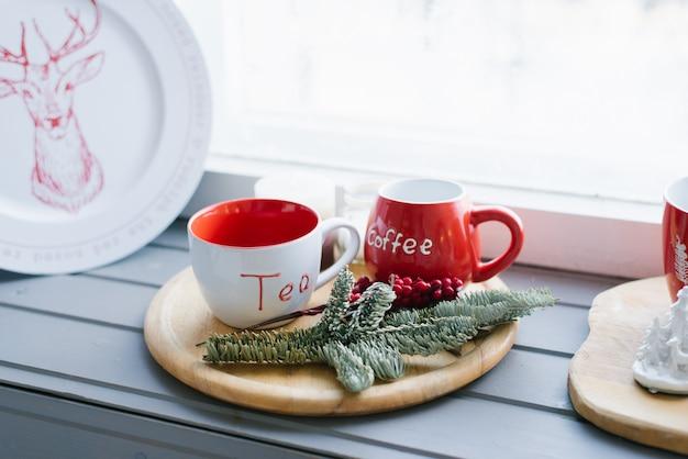Dos tazas rojas en una bandeja de madera en el alféizar de la ventana, decoración navideña
