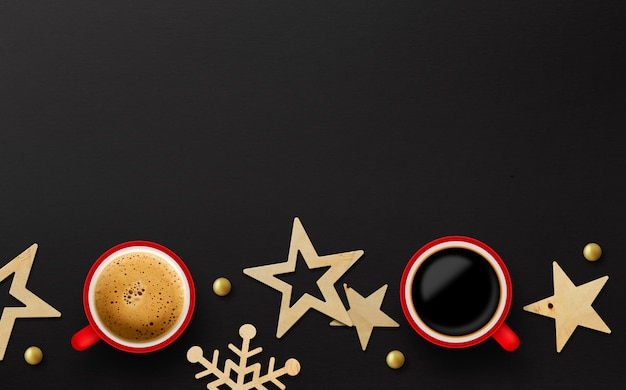 Dos tazas rojas de café y decoración navideña sobre papel negro