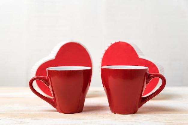 Dos tazas rojas y cajas en forma de corazón. fecha, día de san valentín.