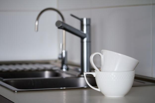 Dos tazas de té blanco limpio cerca del fregadero de metal