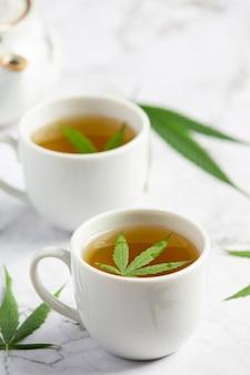 Dos tazas de té de cáñamo con hojas de cáñamo en suelo de mármol blanco