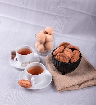 Dos tazas de té con galletas y chocolate.
