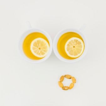 Dos tazas de té de jengibre con una rodaja de limón y almendras aisladas sobre fondo blanco