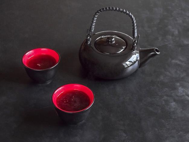 Dos tazas de té rojo y una tetera negra sobre la mesa negra.