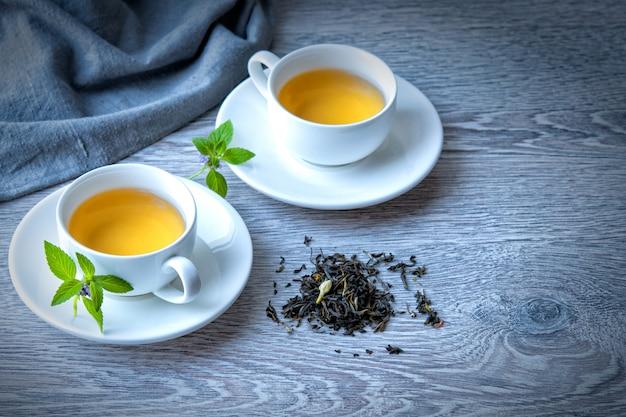 Dos tazas de té verde en una mesa gris