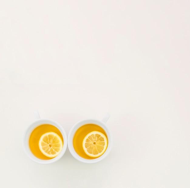 Dos tazas de té verde con una rodaja de limón sobre fondo blanco