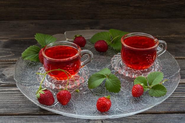 En dos tazas transparentes una bebida de fresa en un plato grande transparente
