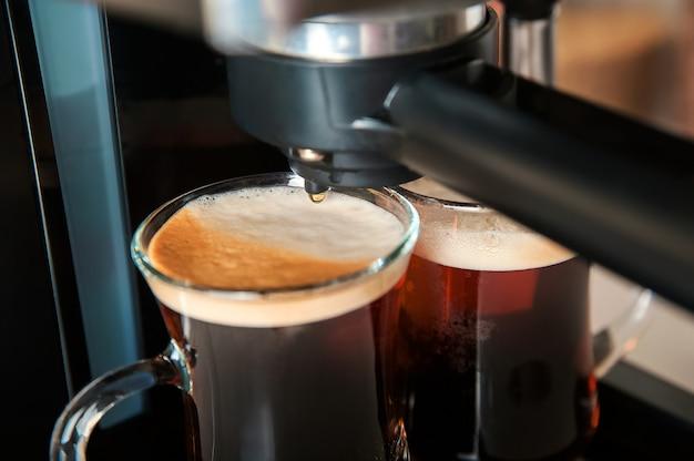 Dos tazas transparentes de café closeup vista frontal cafetera casera y proceso de preparación de la bebida de café espacio de copia