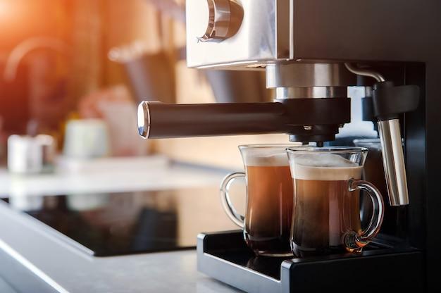 Dos tazas transparentes closeup vista frontal cafetera casera y proceso de elaboración de la bebida de café