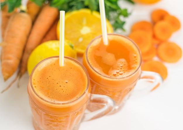 Dos tazas de vidrio con un batido de zanahoria en una mesa de madera blanca.