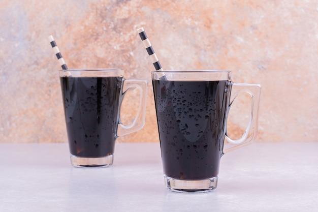 Dos tazas de vino tinto sobre superficie gris