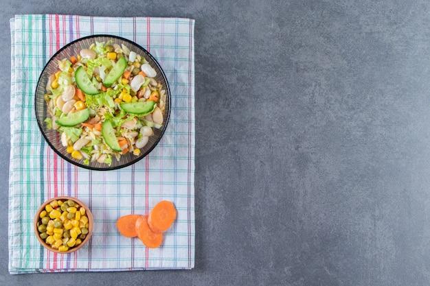 Dos tazones de fuente de ensalada de verduras y zanahoria en rodajas sobre un paño de cocina, sobre la superficie de mármol