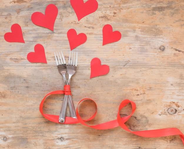 Dos tenedores con corazones de papel.