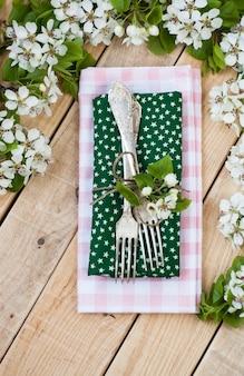 Dos tenedores sobre superficie de madera rústica y ramas con flores.