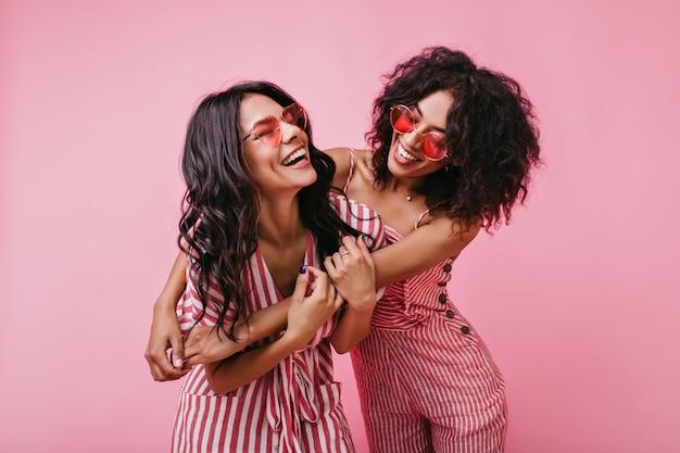 Dos tiernas jovencitas. las modelos alegres y traviesas con piel oscura y rizos disfrutan de una excelente sesión de fotos.