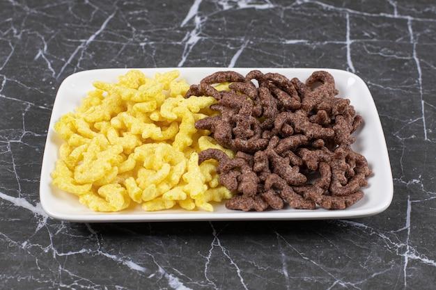 Dos tipos de copos de cereales en un plato blanco.