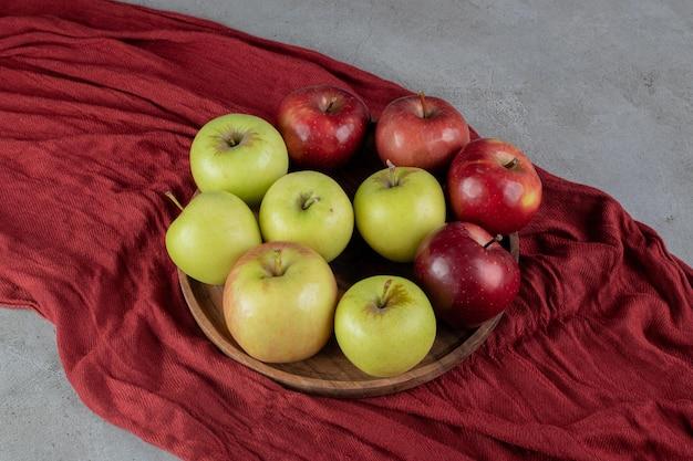 Dos tipos diferentes de manzanas en una bandeja sobre la superficie de mármol.