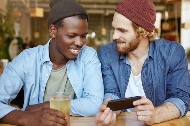 Dos tipos de diferentes razas bebiendo cerveza en el pub. chico blanco de aspecto moderno con barba espesa que tiene una conversación agradable con su amigo