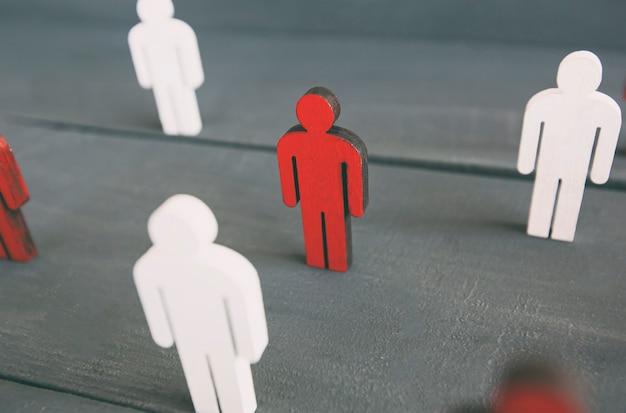 Dos tipos de personas de madera en la mesa de madera: rojo y blanco.