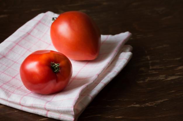 Dos tomates rojos grandes frescos sobre papel de cocina