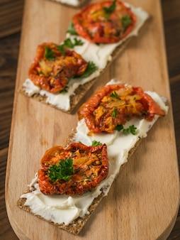 Dos tostadas de pan sobre una tabla de cortar con queso crema y tomates secados al sol sobre una mesa de madera. bocadillo vegetariano de requesón y tomates.