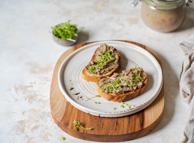 Dos tostadas rillettes de pollo (paté) en pan blanco con brotes en plato blanco sobre una tabla para cortar madera. copyspace