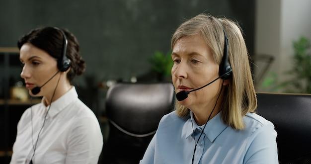 Dos trabajadoras de call center sentadas a la mesa, escribiendo en los teclados de las computadoras y hablando con los clientes en auriculares.
