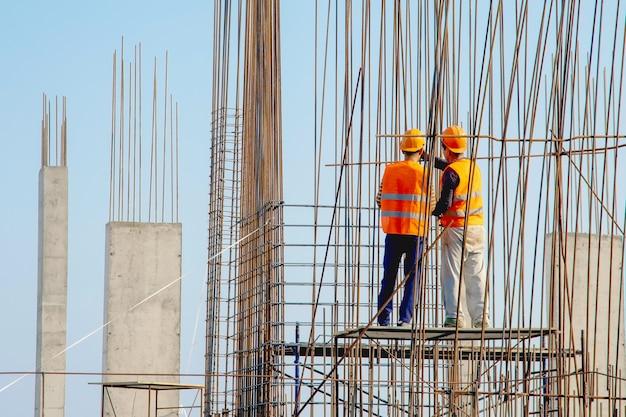 Dos trabajadores de la construcción en monos trabajando en sitio en construcción