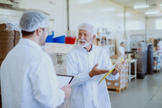 Dos trabajadores de control de calidad con uniformes blancos estériles comparando datos. el más viejo apunta a los documentos en la carpeta mientras que el más joven sostiene la tableta. interior de la planta de alimentos.