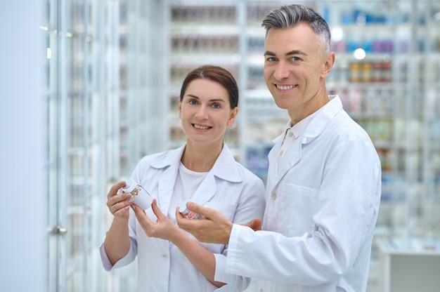 Dos trabajadores de farmacia sonrientes con frascos de medicamentos en sus manos